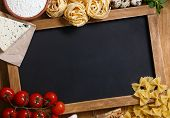 Italian food on vintage wood background with chalkboard