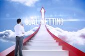 The word goal setting and businessman holding glasses against red steps arrow pointing up against sky