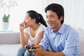 Woman being ignored by boyfriend playing video games at home in the living room