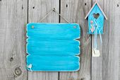 Antique blank blue sign with blue and pink birdhouse and wood hearts hanging on fence