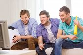 friendship, sports and entertainment concept - happy male friends with football and vuvuzela supporting football team at home