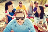 summer, holidays, vacation and happiness concept - smiling man in sunglasses having fun on the beach
