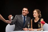 restaurant, couple and holiday concept - smiling couple paying for dinner with credit card at restau