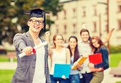 education, campus and teenage concept - smiling teenage boy in corner-cap and eyeglasses with diploma and classmates on the back
