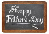 happy father's day in white chalk on a vintage slate blackboard