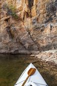 pic of horsetooth reservoir  - canoe bow with a paddle on Horsetooth Reservoir with a high sandstone cliff - JPG