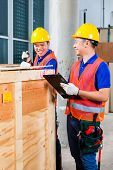 Two Asian Indonesian industrial or construction workers controlling with a checklist a delivery on a