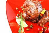 roast beef meat fillet medallion with cherry tomatoes and hot peppers on red plate isolated on white