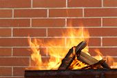 burning wood in a brazier on the brick wall background
