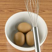 Whisk And Egg In White Bowl