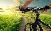 foto of exercise bike  - Man with bicycle riding country road - JPG
