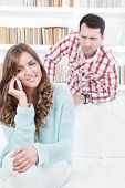 Jealous Worried Man Peering Over The Shoulder Of His Girlfriend