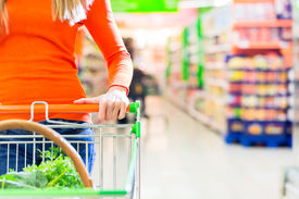 stock photo of grocery cart  - Woman driving shopping cart while grocery shopping in supermarket  - JPG