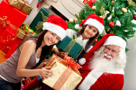 stock photo of santa claus hat  - Santa Claus giving presents to some girls - JPG
