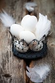 Colorful easter eggs in basket with white feathers