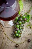 Glass of red wine with bunch of grapes