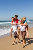 foto of family vacations  - a family of four with the parents giving their teen kids piggyback rides on the beach - JPG