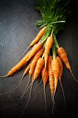 Bunch of fresh carrots on dark background