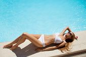 picture of sunbather  - Young woman sunbathing near swimming pool - JPG
