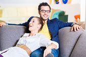 Young couple selecting together sofa in furniture store to furnish home