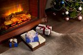 Christmas gift boxes and New Year tree in the interior with fireplace