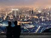 Silhouette of couple sit on ground point faraway on the roof above the city in the night.