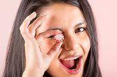 beautiful young hispanic girl eating candy sweets caramel
