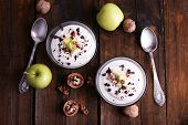 Oatmeal with yogurt in bowls, apples and walnuts on brown wooden background