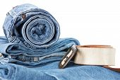 Stack of blue jane and leather belt isolated on a white background