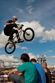 BMX Rider Performs Stunt Over Three Audience Members At Fair