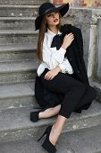 Beautiful Ladylike Woman In Elegant Clothes Sitting On Stairs In Park