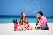 stock photo of family vacations  - Family of four having fun on tropical beach - JPG