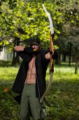 picture of longbow  - Beard Man With A Bow And Arrows In The Woods - JPG