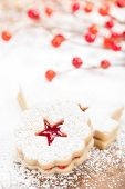 picture of linzer  - Christmas Linzer cookie with powdered icing sugar and red decorations in the background - JPG