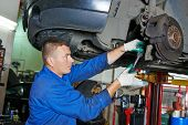 pic of suspension  - car mechanic worker repairing suspension of lifted automobile at auto repair garage shop station - JPG