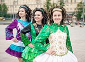 Three Women In Irish Dance Dresses And Wig Posing