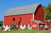 foto of red barn  - A summer image of a red barn with grain conveyor coming out of a side window - JPG