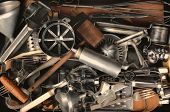 Closeup of a group of old metal and wood kitchen utensils. Items include: sifter, funnel, cookie cutters, forks, mallet, corkscrew, mixer, beater, whisk, press, spoon, grater and more.