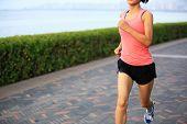 Runner athlete running at seaside. woman fitness jogging workout wellness concept.