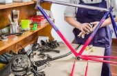 Hands of real bicycle mechanic cleaning frame bike