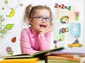 stock photo of kindergarten  - Funny smart kid in eyeglasses reading book in kindergarten - JPG