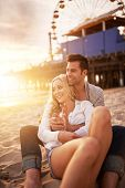 pic of couple sitting beach  - couple sitting in the sand on the beach near santa monica pier in california usa at sunset with bright golden lens flare - JPG