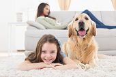 picture of dog-house  - Portrait of happy girl with dog lying on rug while mother relaxing at home - JPG