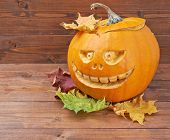 pic of jack-o-lantern  - Scary jack o lantern pumpkin composition next to colorful maple leaves over the wooden boards surface - JPG