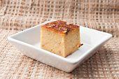 """foto of custard  - """"Mung Bean Thai Custard Dessert Recipe Khanom Maw Kaeng""""(thai name) made with eggs and pumpkin Ancient thai dessert in white bowl on fabric - JPG"""