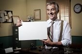 image of 1950s  - Cheerful businessman showing a blank sign and smiling 1950s office on background.
