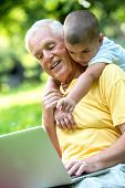 stock photo of grandfather  - happy elderly senior grandfather and child in park using laptop computer - JPG