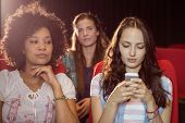 stock photo of annoyance  - Annoying woman texting during movie at the cinema - JPG