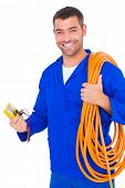 stock photo of  multimeter  - Portrait of smiling electrician with wire roll and multimeter on white background - JPG