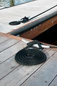 pic of dock  - Black ropes coiled on a wooden dock and tied to a metal dock cleats - JPG